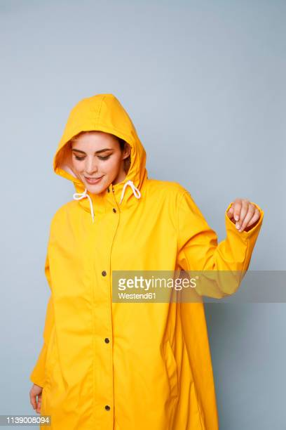 smiling young woman wearing yellow rain coat in front of blue background dancing - yellow coat stock pictures, royalty-free photos & images