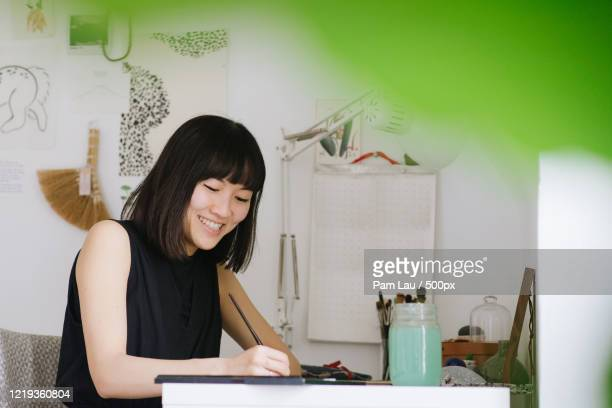 smiling young woman while painting - showus stock pictures, royalty-free photos & images