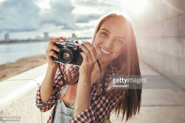 smiling young woman with a camera at the riverside - camera photographic equipment - fotografias e filmes do acervo