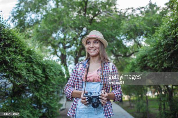 smiling young woman with a camera in a park - sorriso aberto imagens e fotografias de stock