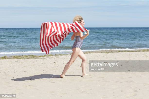 Smiling young woman with beach towel in front of the sea