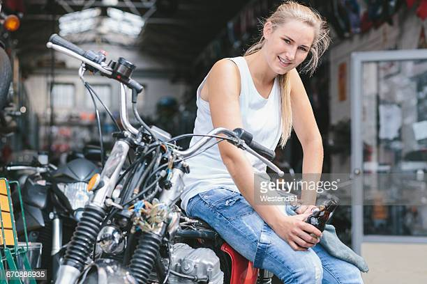 Smiling young woman with beer bottle on motorbike