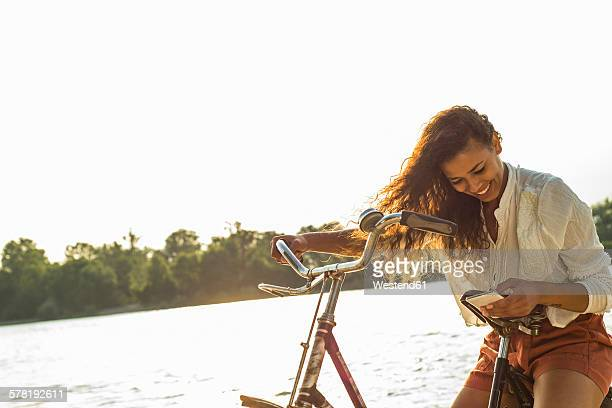 Smiling young woman with bicycle and cell phone by the riverside