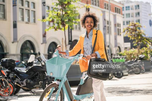smiling young woman with bicycle in the city on the go - shoulder bag stock pictures, royalty-free photos & images