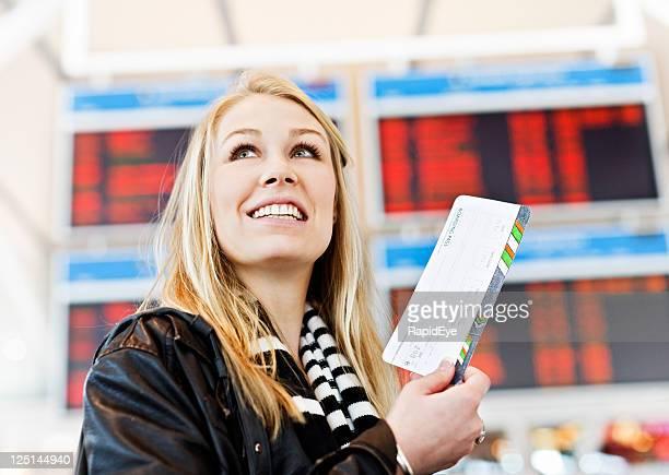 Sonriente mujer joven con tarjetas de embarque para el aeropuerto a la explanada