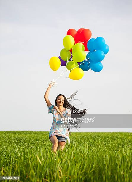 Smiling young woman with brunch of balloons jumping in grassland