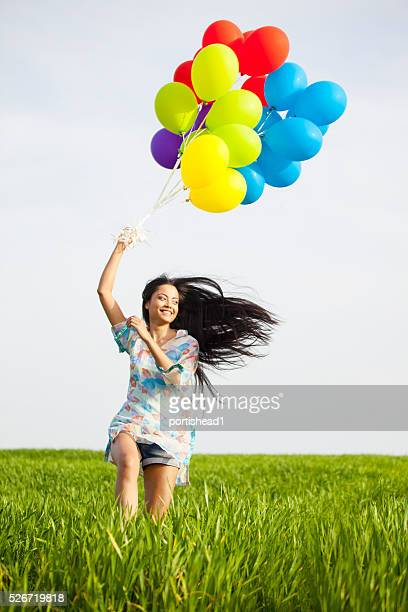Smiling young woman with brunch of balloons running in grassland-close-up