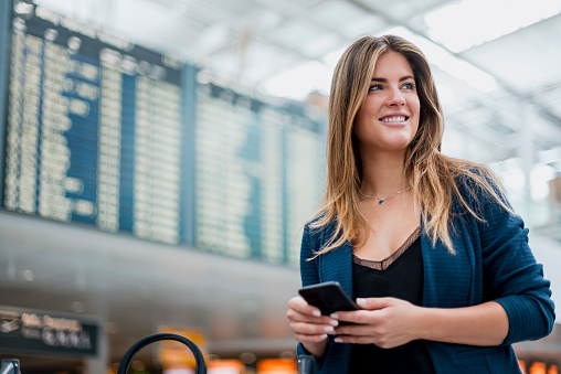 Smiling young woman with cell phone at departure board looking around - gettyimageskorea