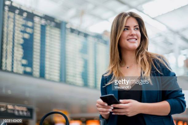 smiling young woman with cell phone at departure board looking around - geschäftsreise stock-fotos und bilder