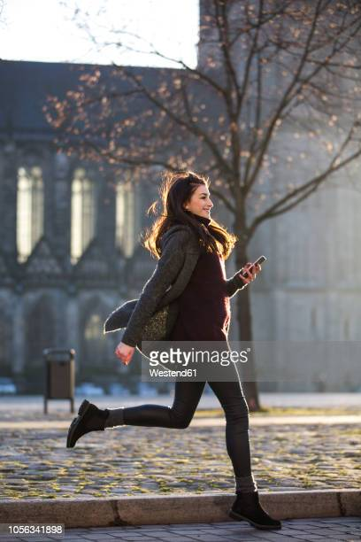 smiling young woman with cell phone crossing the street - fast fashion stock pictures, royalty-free photos & images