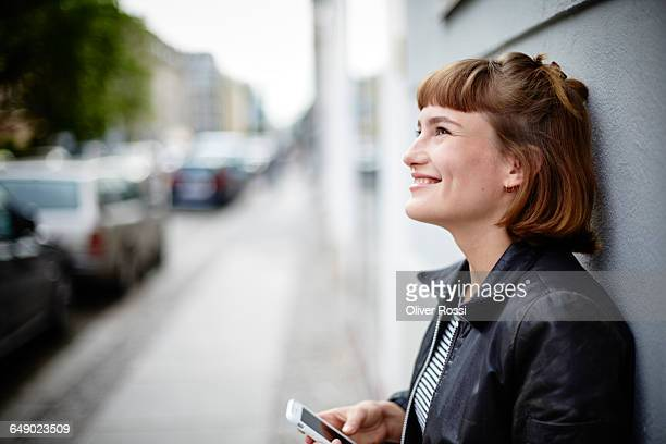 Smiling young woman with cell phone outdoors