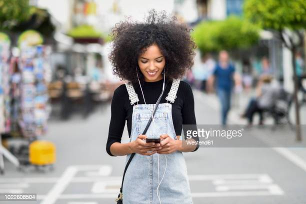 smiling young woman with earphones looking at cell phone - crossbody bag stock pictures, royalty-free photos & images