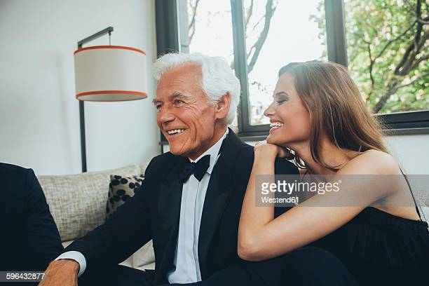 smiling young woman with elegant senior man on couch - may december romance stock photos and pictures