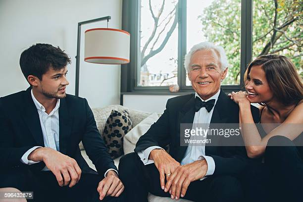 Smiling young woman with elegant senior man talking to young man on couch