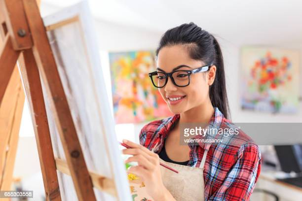 Smiling young woman with eyeglasses drawing