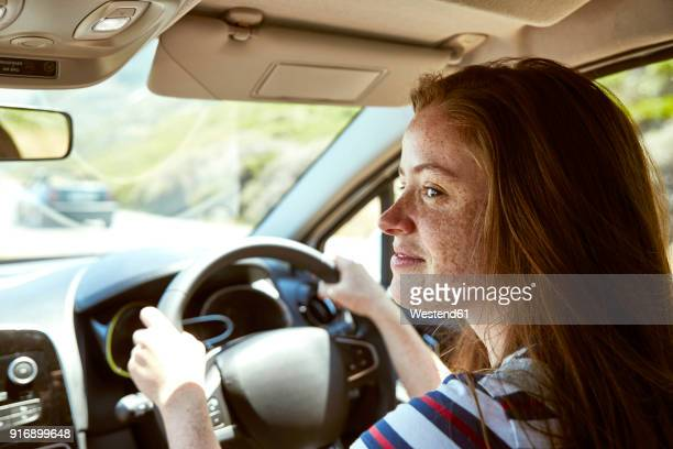 Smiling young woman with freckles driving car looking sideways