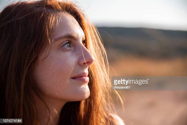 smiling young woman with freckles looking away - natural beauty people stock pictures, royalty-free photos & images
