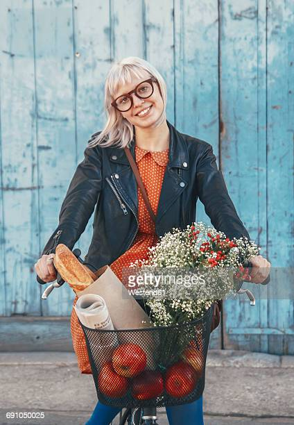 smiling young woman with groceries on bicycle - baguette photos et images de collection