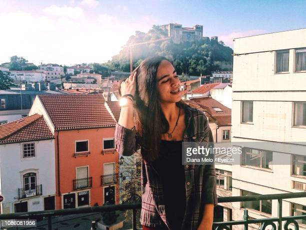 smiling young woman with hand in hair standing against buildings in city - leiria district stock photos and pictures