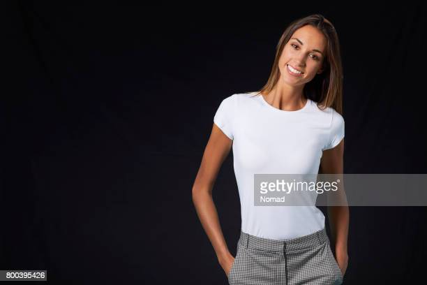 smiling young woman with hands in pockets - all shirts stock pictures, royalty-free photos & images