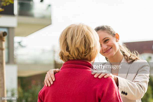 smiling young woman with hands on shoulders of her grandmother - doing a favor stock pictures, royalty-free photos & images