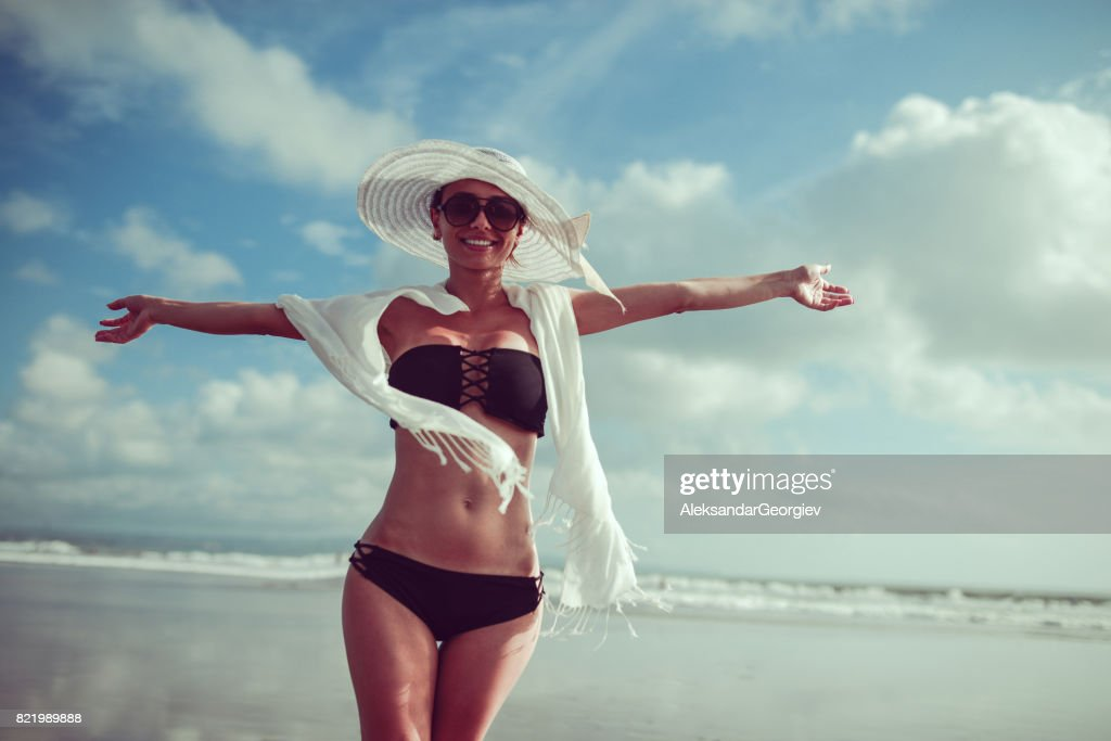 Smiling Young Woman With Hat and Sunglasses Posing With Raised Hands At Ocean Beach in Bali : Stock Photo
