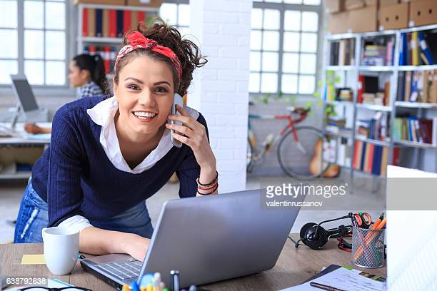 Smiling young woman with headband talking on smart phone