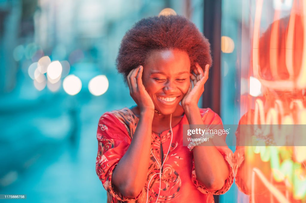 Smiling young woman with headphones standing next to neon light : Stock Photo