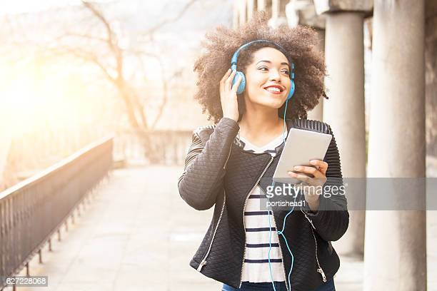Smiling young woman with headphones walking near columns