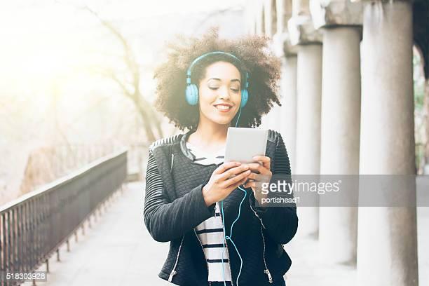 Sonriente mujer joven con auriculares caminando por la calle