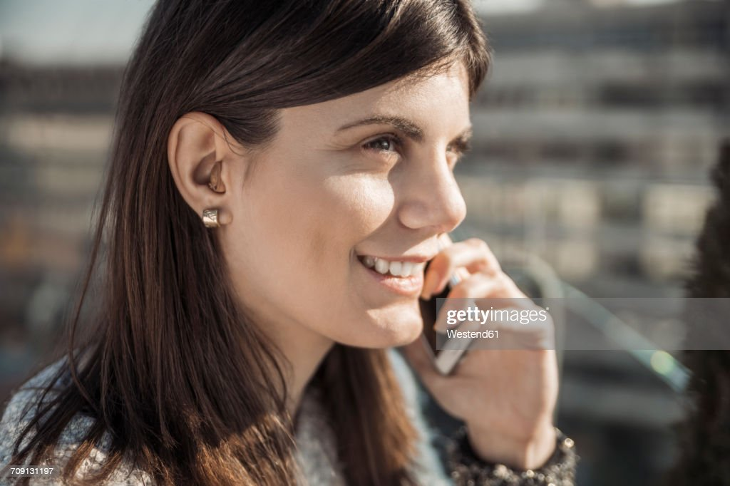 Smiling young woman with hearing aid on the phone : Stock Photo