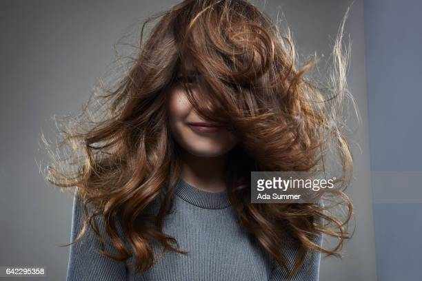 smiling young woman with long messy brown hair - windzerzaustes haar stock-fotos und bilder