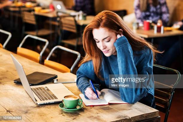 smiling young woman with long red hair sitting at table, working on laptop computer. - hot desking stock pictures, royalty-free photos & images