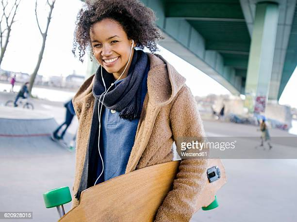 Smiling young woman with longboard hearing music with earphones
