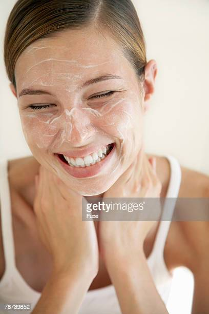 Smiling Young Woman with Lotion on Face