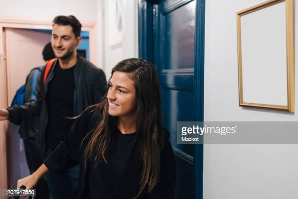 smiling young woman with male friends arriving at rental apartment - ankunft stock-fotos und bilder