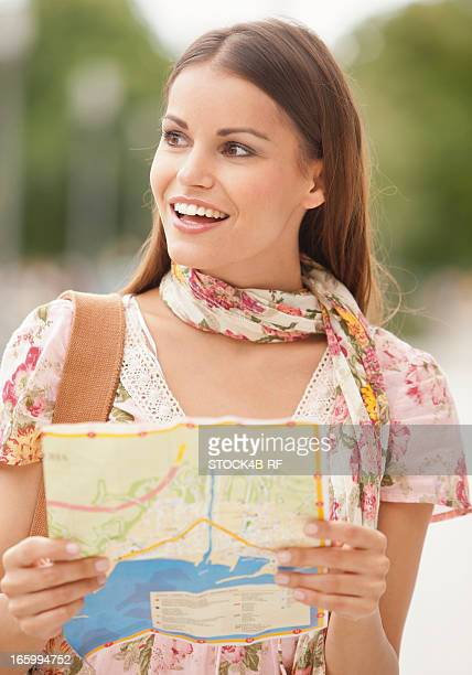 Smiling young woman with map