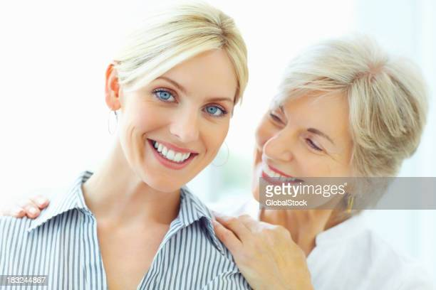 Smiling young woman with mother against white background