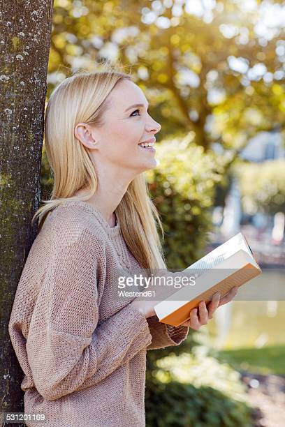 Smiling young woman with opened book leaning at tree trunk