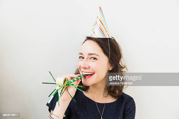 Smiling young woman with party horn blower