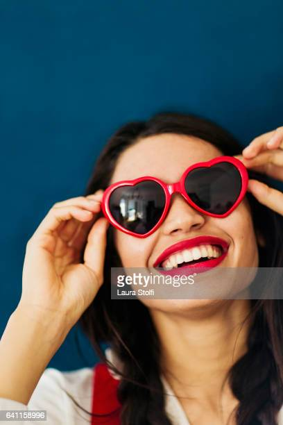Smiling young woman with red heart shaped sunglasses