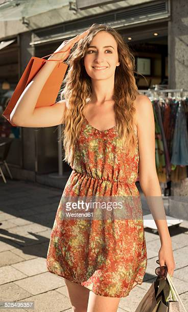 Smiling young woman with shopping bags standing in evening twilight