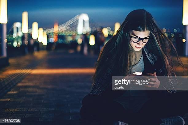 Souriante jeune femme avec le téléphone intelligent de nuit