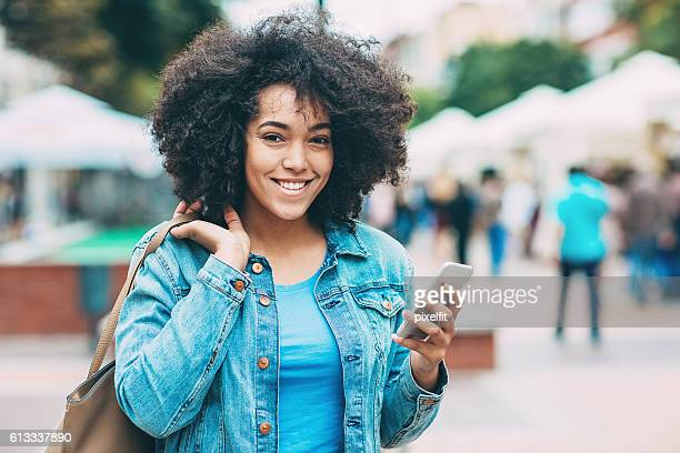 smiling young woman with smart phone - creole ethnicity stock pictures, royalty-free photos & images