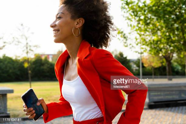 smiling young woman with smartphone wearing fashionable red pantsuit - red suit stock pictures, royalty-free photos & images