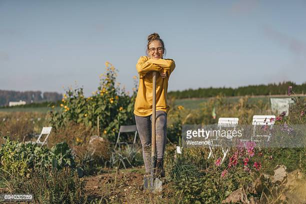 Smiling young woman with spade in cottage garden