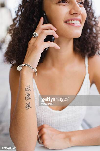 Smiling young woman with tattoo on forearm on the phone