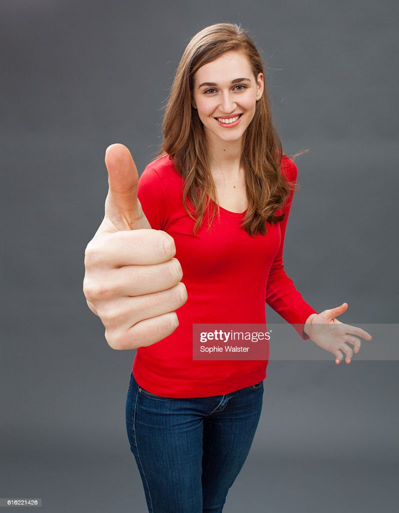 smiling young woman with thumbs up for symbol of satisfaction : Stock-Foto