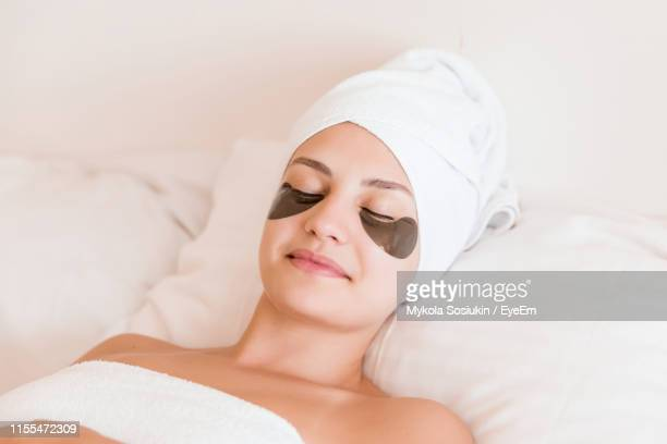 smiling young woman with under eye patches lying on bed at spa - beauty salon ukraine stock pictures, royalty-free photos & images
