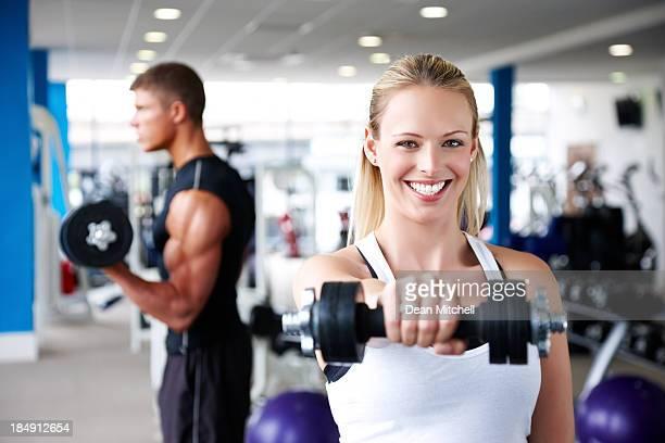 Lächelnde Junge Frau mit Hanteln im Fitnessstudio